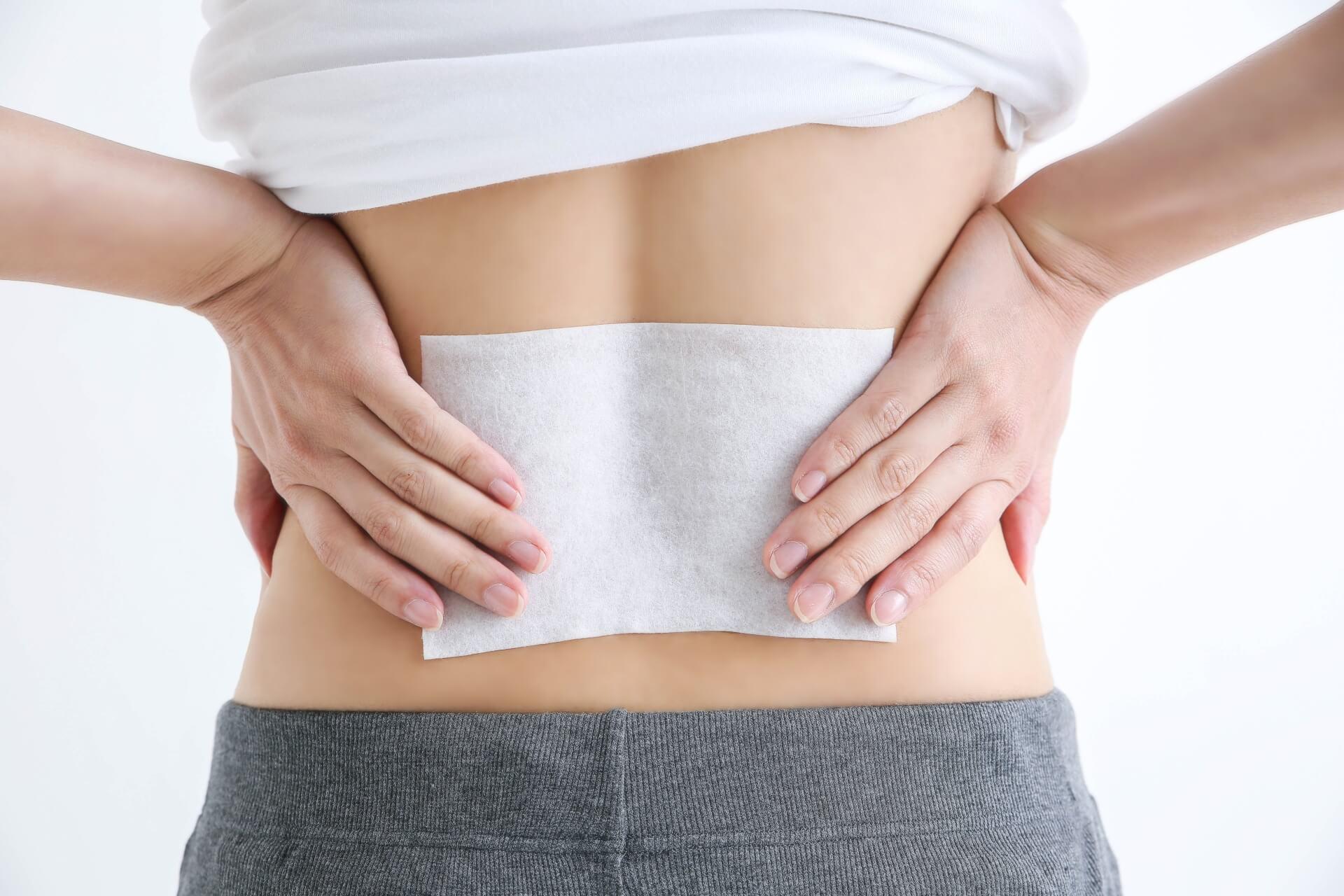 肩こり・腰痛に湿布をしている女性